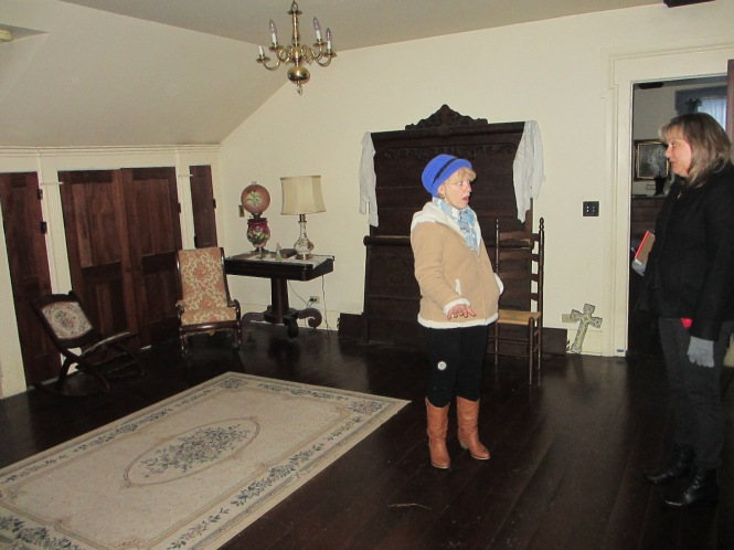 A light sphere is seen under Kathy's hand during a tour of the house.